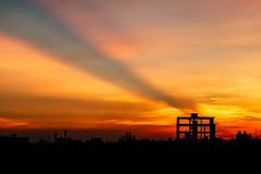 Setting sun behind construction building Stock Images
