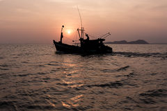 Setting sun behind a fishing boat. Royalty Free Stock Images