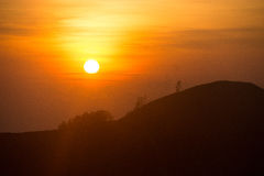 Setting sun behind mountain range. Orange to yellow sunset with outlining of a mountain range with trees Stock Photos