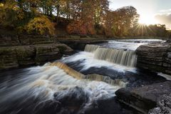 Aysgarth Lower Falls. The setting sun breaks through the trees at Aysgarth Falls Stock Photography