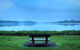 Lonely bench overlooking peaceful landscape stock photography