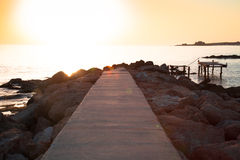 Setting sun with a broken pier in Paphos. with glare Royalty Free Stock Photo