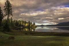 Setting sun casts light on fall colors reflected in Lake Quinault. Stock Photos