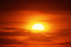Setting sun into clouds Stock Photography