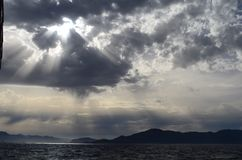 The setting sun in the clouds over the Aegean Sea. View of the setting sun in the clouds over the Aegean Sea royalty free stock photos