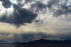 The setting sun in the clouds over the Aegean Sea. View of the setting sun in the clouds over the Aegean Sea stock photo