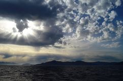 The setting sun in the clouds over the Aegean Sea. View of the setting sun in the clouds over the Aegean Sea stock photos