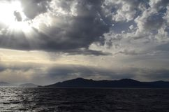 The setting sun in the clouds over the Aegean Sea. View of the setting sun in the clouds over the Aegean Sea stock images