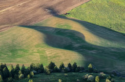 Setting sun creates long shadows on rolling hills Royalty Free Stock Image