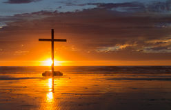 Setting Sun Cross. Cross on a beach with the sun setting down behind it Royalty Free Stock Photography