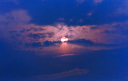 The setting sun on the dark blue sky hiding in the clouds Royalty Free Stock Photography
