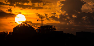 Setting sun dipping behind scaffolding Royalty Free Stock Photos