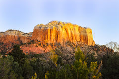 Setting Sun hits the side of a hill in Ghost Ranch of New Mexico stock image