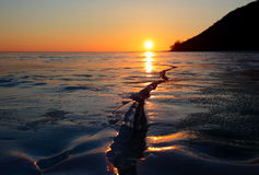 The setting sun on the horizon of lake Baikal in winter. The sun goes behind the distant rocky promontory of the coast of Baikal lake, covered with ice crust in Royalty Free Stock Photos