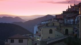 The setting sun illuminates the roofs of a medieval town in the mountains. Perinaldo, Italy stock video