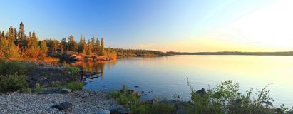 Pebble Beach and Canadian Shield at Frame Lake, Yellowknife, Northwest Territories. The setting sun is illuminating the outcroppings of Precambrian rock from the Stock Photography