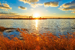 The setting sun lake pumping unit Royalty Free Stock Photo