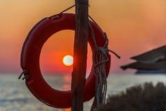 Sunset in life belt on beach. The setting sun in life belt on beach stock photos