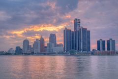 Detroit, Michigan Skyline Backlit By Sunset. The setting sun lights up the clouds behind the skyline of downtown Detroit, Michigan. The spectacle is reflected in royalty free stock photography