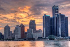 Detroit, Michigan Skyline Backlit By Sunset Colors. The setting sun lights up the clouds behind the skyline of downtown Detroit, Michigan. The spectacle is stock photo