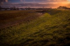Farm on the dike. Setting sun over a field Royalty Free Stock Image