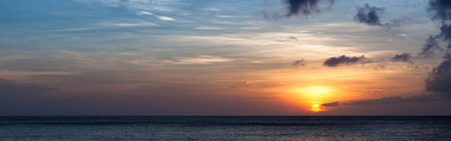 Setting sun over ocean horizon panorama Stock Images