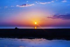 Setting sun over sea horizon Stock Photos