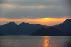 Setting sun peeking out from the clouds in Ha Long Bay, landscape view Royalty Free Stock Photo