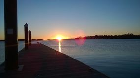Setting sun on the pier royalty free stock photo