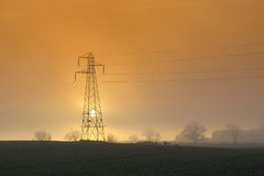 Setting sun with pylon Royalty Free Stock Images