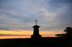 Long Point lighthouse; Cayuga Lake; golden sunset. Setting sun reflects a golden glow over the calm lake water behind the small lighthouse on the shoreline Royalty Free Stock Images