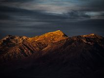 Setting sun reflects golden orange light on the tops of the mountain peaks in Utah royalty free stock images