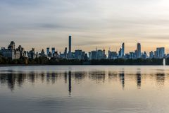 Sunset Reflections of Midtown Manhattan. The setting sun reflects to towers of New York City`s Midtown Manhattan in the waters of Central Park`s Jaqueline royalty free stock images
