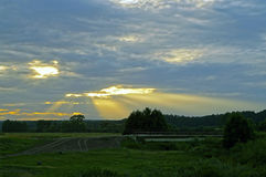 The setting sun shines through the clouds. The setting sun shines through the clouds and illuminates the rural landscape Royalty Free Stock Photo