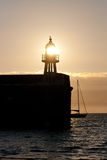 The setting sun shines through a lighthouse on a Port Erin Harbour Stock Image