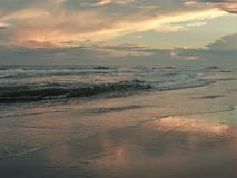 Atlantic Beach Sunset. Setting sun shines off of clouds and reflects off the sand and waves in Atlantic Beach, North Carolina Royalty Free Stock Photography