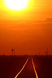 Setting sun shining on railroad tracks Royalty Free Stock Photo