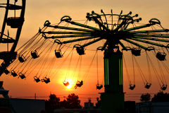 Setting sun and swings. Swing ride at the kentucky state fair silhouetted against the setting sun stock image