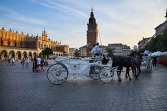 Setting sun on the Town Hall Tower and the Cloth Hall on Market Square in Krakow Poland Royalty Free Stock Photo