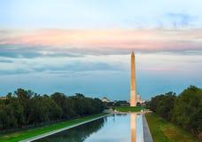 Setting sun on Washington monument reflecting stock photo
