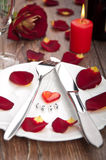 Setting table for valentines day with petals Royalty Free Stock Images