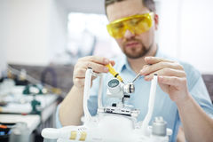 Setting Up Camera to Drone Surveillance System. Man in orange protective mask working on assembling new spy system connecting quadcopter drone and action camera royalty free stock photography
