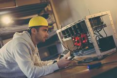 Setting up mining rig electrical energy consumption. Programmer setting up a mining rig for cryptocurrency mining, holding a wattmeter, measuring electrical stock photography