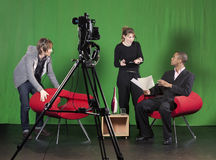 Setting up for a TV Recording. A crew member arranges furniture whilst the floor manager talks to the presenter on a TV studio set. TV camera on a tripod out-of stock photo
