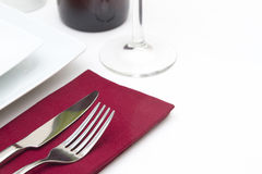 Setting with white plates and red wine with red na Royalty Free Stock Photos