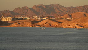 Settlement on the deserted beach. On the horizon there are mountains. In the sea there is a boat stock footage