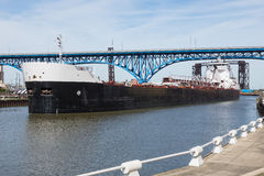 Settler's Landing. A Great Lakes bulk carrier ship cruises slowly past the Settler's Landing park located in Cleveland, Ohio on the bank of the Cuyahoga River royalty free stock image