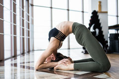 Setu Bandha Sirsasana. Beautiful yoga woman practice near window yoga room studio background. Yoga concept. Stock Image
