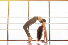Setu Bandha Sirsasana. Beautiful yoga woman practice near window yoga room studio background. Yoga concept. Royalty Free Stock Photo