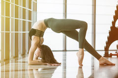 Setu Bandha Sirsasana. Young beautiful woman practicing yoga in yoga studio the background. Stock Photography